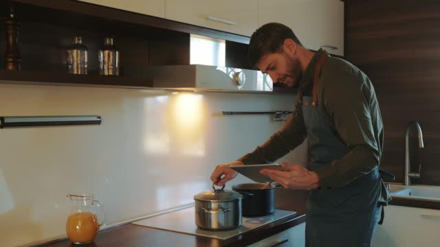 vidéos et rushes de cuisiner un délicieux repas à l'aide d'une recette en ligne - recette