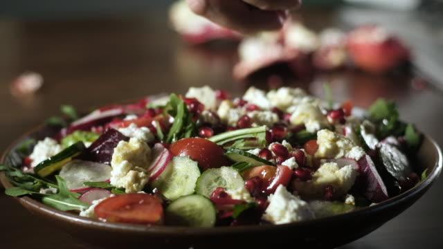 vídeos de stock e filmes b-roll de cooking delicious salad. tomatoes arugula beetroot pomegranate ricotta cucumber. - romã