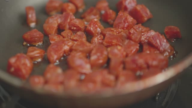 cooking diced chorizo sausage in a pan close up view of cooking diced chorizo sausage in a pan paprika stock videos & royalty-free footage