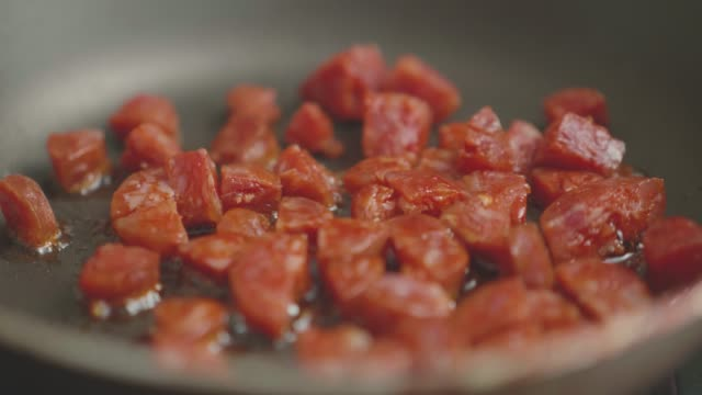 cooking diced chorizo sausage in a pan - paprica video stock e b–roll