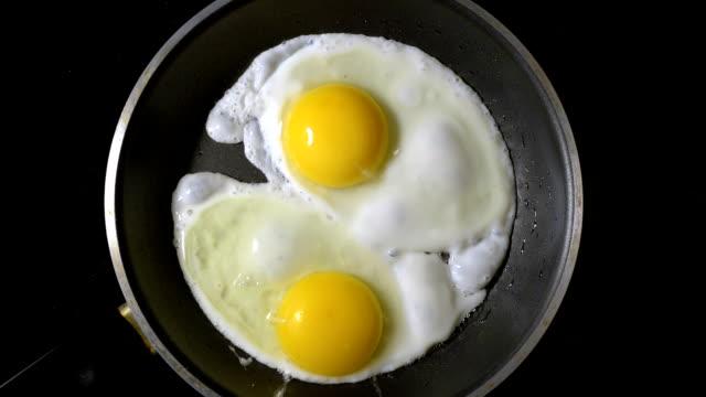 フライパンで卵を調理します。時間の経過。平面図です。 - 油料理点の映像素材/bロール