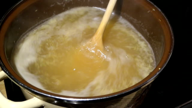 cooking elder beery flower head jam confiture in a pot. filling sugar into the pot. - sciroppo video stock e b–roll