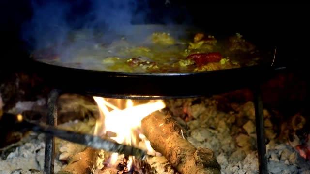 i̇spanya'da geleneksel olarak odun pirinci pişirmek. - şömine odunu stok videoları ve detay görüntü çekimi