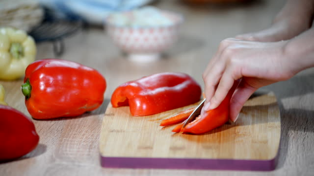 Cooking, food and home concept - close up of male hand cutting pepper on cutting board at home.
