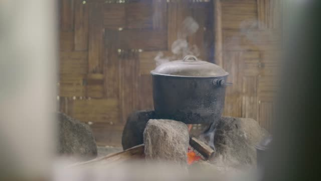 Cooking food in pot on bonfire on wooden wall background. Preparing dinner on fire in kettle in traditional asian village.