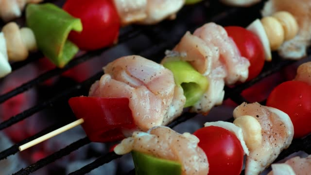 Cooking Fresh Vegetables And Marinated Meat On Bamboo Sticks On Barbecue Grill With Fire And Smoking Closeup