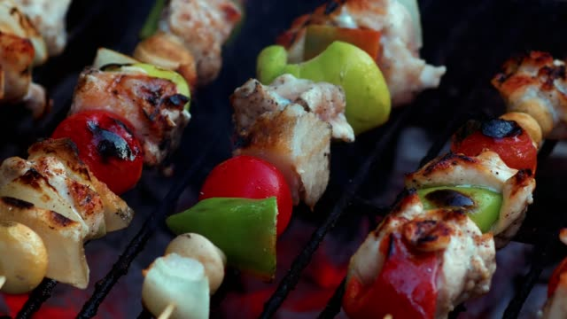 cooking fresh vegetables and marinated meat on bamboo sticks on barbecue grill with fire and smoking closeup - spiedino video stock e b–roll