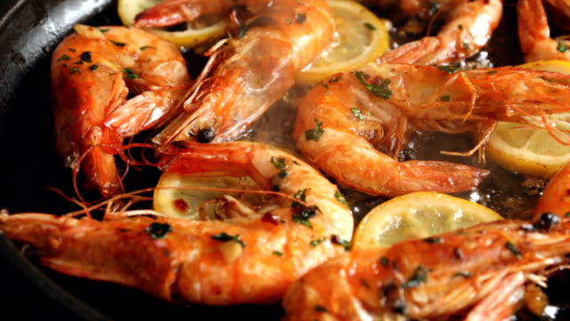 cooking fried roasted shrimps in frying pan with lemon greens parsley garlic video