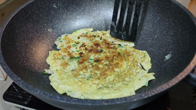 Cooking frying omelette on electric pan for lunch, slow motion
