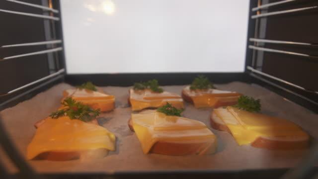 オーブン タイムラプスのチーズのパンを焼き料理 - チーズ 溶ける点の映像素材/bロール