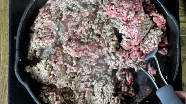 Cooking ground beef Overhead view of hamburger simmering in a cast iron skillet ground beef stock videos & royalty-free footage