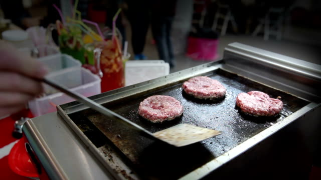 Cooking hamburgers. The cook turns the meat on the stove. video