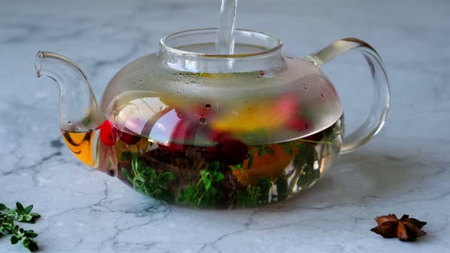 Cooking immunity boosting drink. Boiling water brews tea with orange, cranberry, thyme and cinnamon close-up