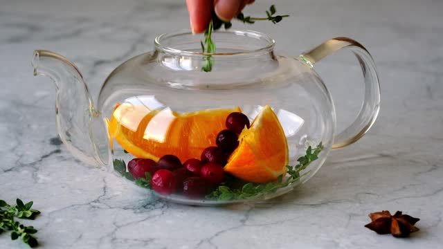 Cooking immunity boosting drink. Ingredients in glass teapot: oranges, cranberries and thyme close-up