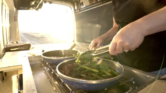 cooking in a camper at dinnertime - fianco a fianco video stock e b–roll