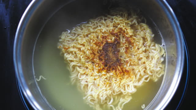 cooking, instant noodles boiling in frying pan, close up video