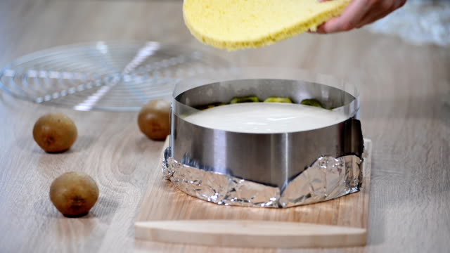 cooking kiwi mousse cake with sponge cake. - formaggio spalmabile video stock e b–roll