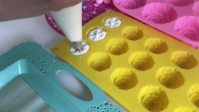 vídeos y material grabado en eventos de stock de cocinar malvaviscos. una mujer que usa una bolsa de pastelería y una boquilla llena el formulario de silicona con un malvavisco. - suflé