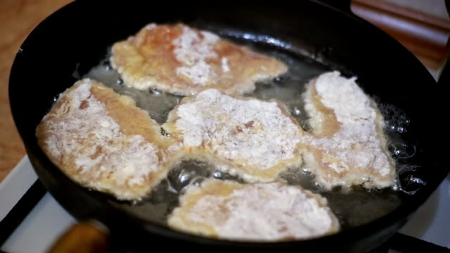 cooking meat chops in a frying pan in the home kitchen. slow motion - posizione corretta video stock e b–roll