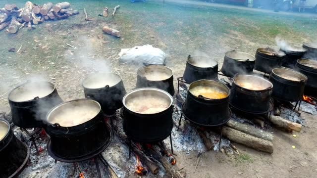 Cooking meat outdoors in cast-iron cauldrons on open campfire, 4k video