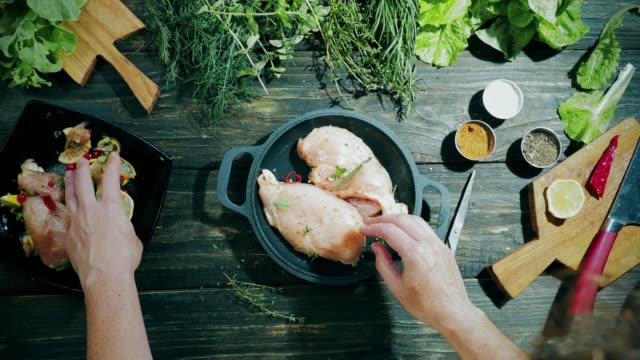 Cooking of chicken breast fillet Cooking of chicken breast fillet marinated with lemon, red currant berries and fresh herbs. Putting marinated fillet into the frying pan. Overhead view fillet stock videos & royalty-free footage
