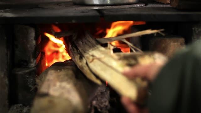 odun sobası üzerinde yemek pişirmek. geleneksel yemek pişirme. - şömine odunu stok videoları ve detay görüntü çekimi