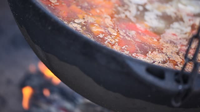 Cooking outside on the fire in a large cauldron. Asian food video