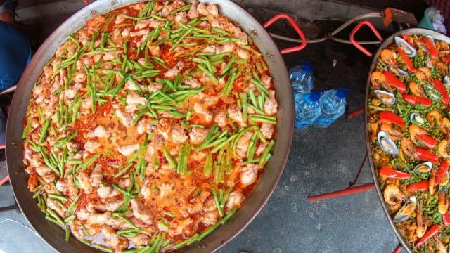vídeos y material grabado en eventos de stock de cocinar paella en el puesto - comida española