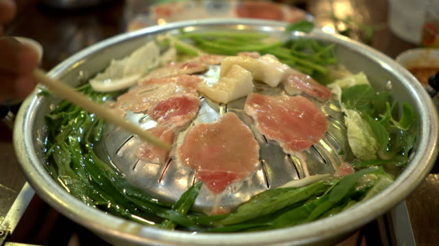 cooking raw pork and fresh vegetable on hot pan as called Moo Kra Ta video