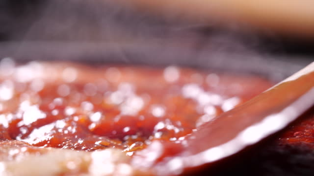 vídeos de stock e filmes b-roll de cooking red tomato sauce in a boiling pan and stirring with steam in 4k resolution - sauce tomatoes