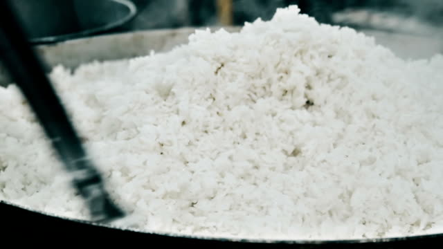 Cooking rice on a pan Close up of a man cooking rice on a pan cooked stock videos & royalty-free footage