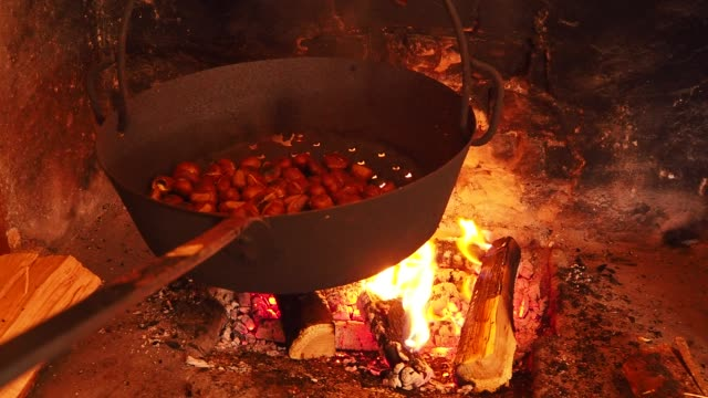 vidéos et rushes de cuisson des châtaignes grillées dans la casserole sur le feu dans un jour d'automne - marron couleur