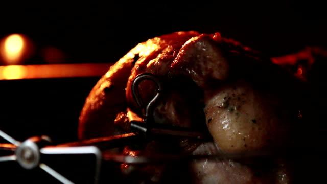 kochen ganze brathähnchen auf der rotisserie spieß in vom grill ofen. brünierte huhn dreht sich während des grillen unter einem grill-element. innenansicht. - fettgebraten stock-videos und b-roll-filmmaterial