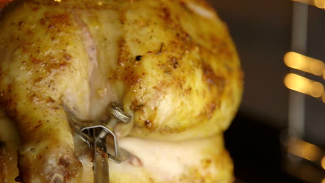 Cooking roasted whole chicken on the rotisserie spit in hot oven closeup video