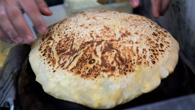 Cooking roti on a hot domed pan video