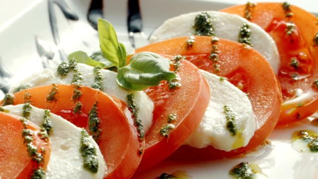 Cooking salad of mozzarella, tomato, greens