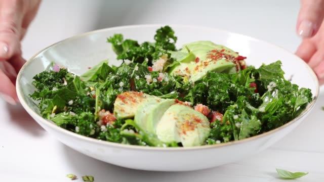 kochsalat mit grünkohl, quinoa, nüssen und avocado in weißer schüssel. gesundes veganes ernährungskonzept. - grünkohl stock-videos und b-roll-filmmaterial