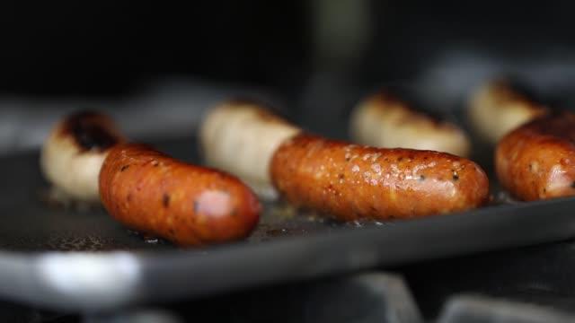 vidéos et rushes de cuisiner des saucisses - aliment frit