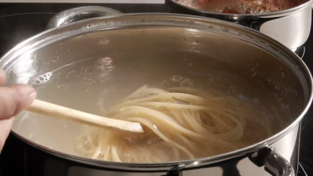 cooking Spaghetti  in boiling water in a metal pan
