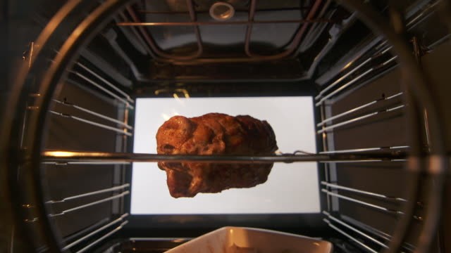 Cooking spit rotisserie pork sirloin roast in hot convection oven timelapse video