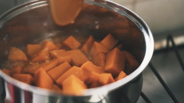 cooking stewed boiling pumpkin stell pan slow motion - zucca video stock e b–roll