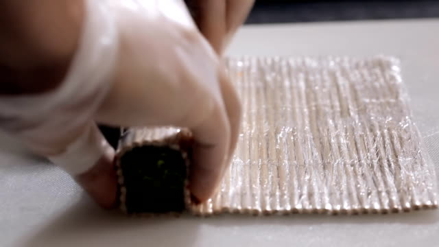 cooking sushi rolls in the studio. forming into a square roll mat video