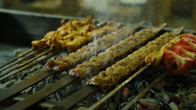 Cooking traditional Turkish adana kebab and shish chicken on grill