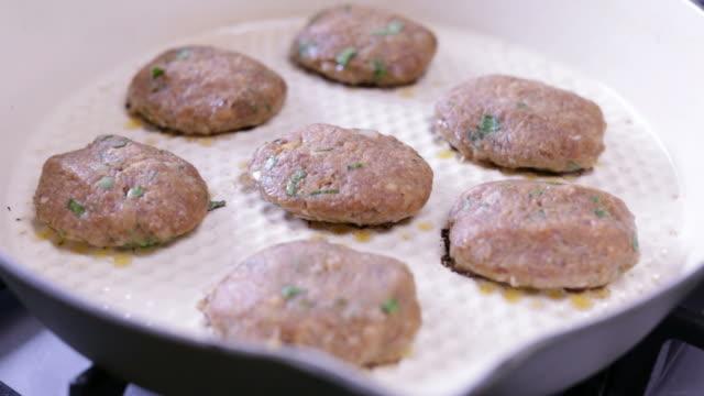 vídeos de stock e filmes b-roll de cooking turkish meatballs in a pan - produto de carne