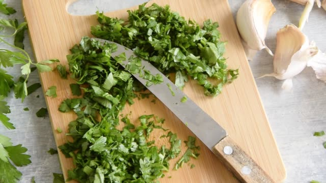 Cooking with greenery, fresh raw parsley and garlic on kitchen table Cooking with greenery, fresh raw parsley and garlic on kitchen table pesto sauce stock videos & royalty-free footage