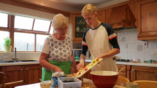 Cooking with her Grandson A teenage boy pours chopped apples into a bowl whilst cooking with his grandmother. grandmother stock videos & royalty-free footage