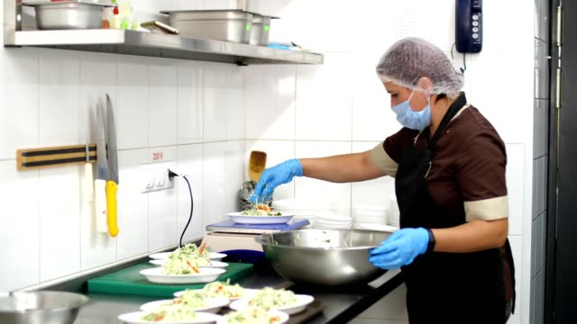 cooking. Woman cook, in protective mask and gloves, puts vegetable salad into small bowl and weighs it on a scale. health food. volunteering and charity. reopening canteen. safety concept