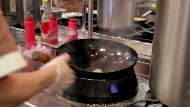 Cooks preparing food on stove frying wok with fire in big modern restaurant kitchen video
