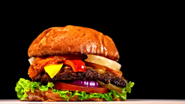 Cool beautiful fresh juicy cooked burger rotate on turntable. Very luscious air bun and marbled beef. Restaurant where each burgers is cooked by hand. Not made ideal. Looks real, loving hand made. video