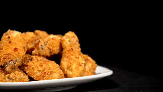 cool vackra färska saftiga kokt kycklingvingar i panering rotera på skivspelare. buffalo wings sprids på mat i vit platta. mycket välsmakande och vackert. matlagning med fritösen fry machine. - marinad bildbanksvideor och videomaterial från bakom kulisserna